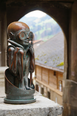 surrealist: Statue of an alien boy in front of H.R. Giger Museum in Gruyeres, Switzerland Editorial