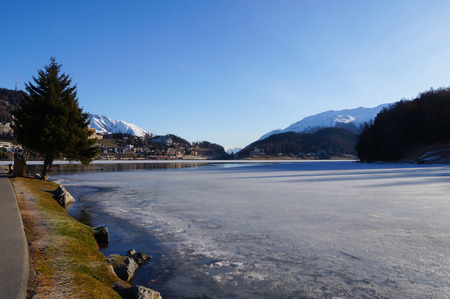 water skiers: Frozen lake and the mountains covered by snow in Switzerland Stock Photo