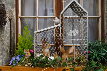 rabbit in cage: A cute cage with rabbit dolls and  eggs in Switzerland Stock Photo