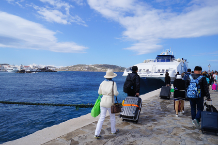 exiting: Mykonos,Greece- April 11,2016:  Unidentified tourists exiting a ferry and walk onto the dock,Mykonos,Greece.