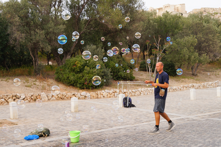 big ball: Athens,Greece- April 14,2016:  Unidentified man making soap bubbles  near Acropolis in Athens,Greece.
