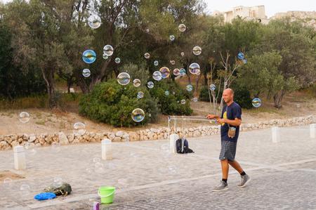 Athens,Greece- April 14,2016:  Unidentified man making soap bubbles  near Acropolis in Athens,Greece.