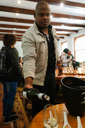 wine testing: Stellenbosch,South Africa - 21 October 2016: Unidentified man pouring white wine at wine tasting table. Shot in Winelands,Stellenbosch, Western Cape, South Africa. Editorial