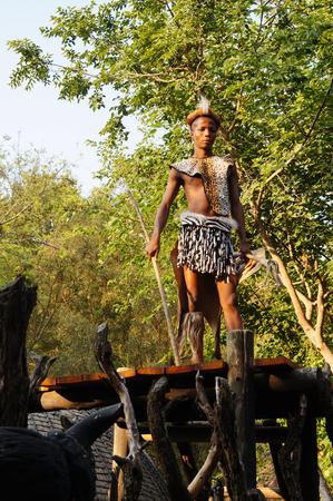 village man: Lesedi Cultural Village, South Africa - 20 October 2016: Zulu man wearing warrior dress near tribal straw house in Lesedi Cultural village, South Africa.