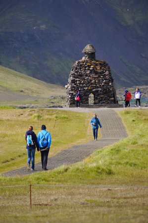 Snaefellsness peninsula,Iceland- 26 June 2017: Unidentified tourists walking near Statue of Bardur Snaefellsnes, half-man, half-giant that is said to roam the Snaefellsnes glacier in Iceland. Editorial