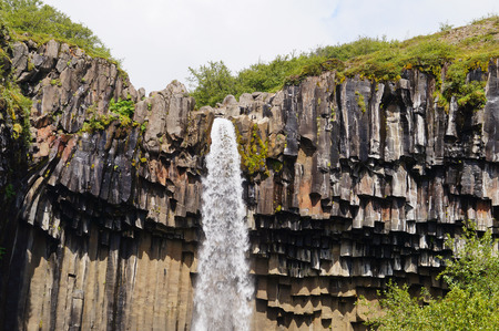 アイスランドの暗い溶岩の柱に囲まれた Svartifoss 滝 写真素材
