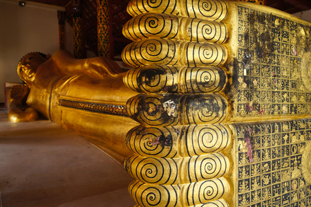 Feet of Reclining Buddha gold statue in Wat Pong Sanuk Tai Temple, Lampang, Northern Thailand.