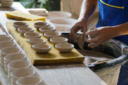 Potter making man put white bowl in glazing liquid ,Northern Thailand.