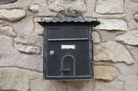 postes: Old postbox on stone wall Stock Photo