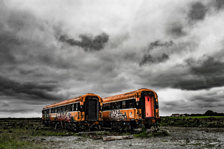 Abandoned train coaches in Ireland under a cloudy sky