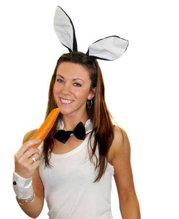 punos: Muchacha del conejito de pascua que come su zanahoria diaria Foto de archivo