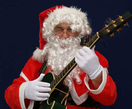 carols: Santa playing christmas carols on guitar