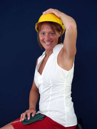 eyecontact: Lady builder trying to keep her hat on         Stock Photo