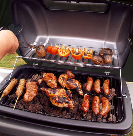 Barbecue with chicken meat and sausages being grilled slowly