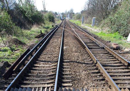 railtrack: Closeup of railtrack with distant station light Stock Photo