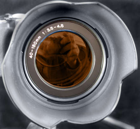 Camera lens showing the photographer inside Stock Photo