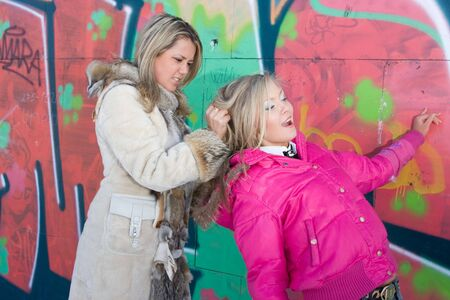 struggle: Two blondes are fighting against a background of graffiti