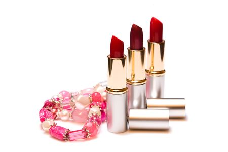 Three red lipstick and womens jewelry on a white background
