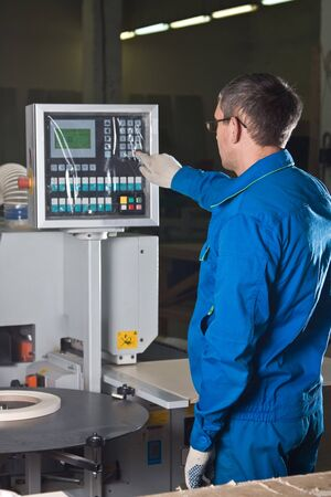 The worker presses buttons of the panel of the machine tool Stock Photo - 4479010