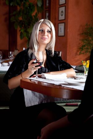 long weekend: Charming blond girl in a restaurant with a glass of red wine