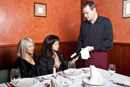 The waiter shows a bottle of wine visitor to the restaurant Stock Photo - 4640912