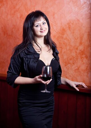 A young woman stands against the wall with a glass of red wine