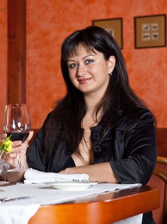 long drink: Charming  brunette girl in a restaurant with a glass of red wine Stock Photo