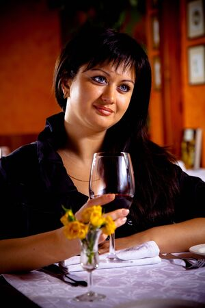long weekend: Charming brunette girl in a restaurant with a glass of red wine