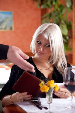 Blond girl in a restaurant show a huge bill for food Stock Photo