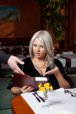 show bill: Blond girl in a restaurant show a huge bill for food Stock Photo