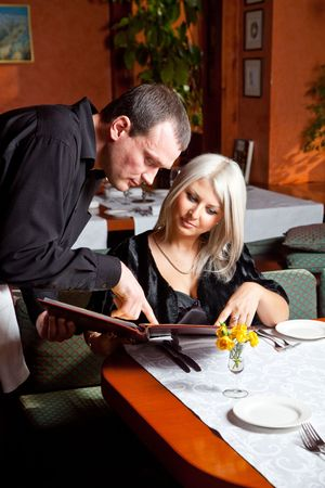 The waiter helped visitor with a choice of eating in a restaurant Standard-Bild