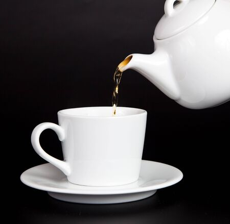 Pour tea from the teapot into the cup on a black background