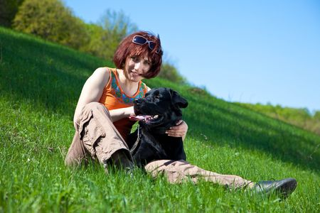 The young woman with black labrador on a green grass Stock Photo - 4831175
