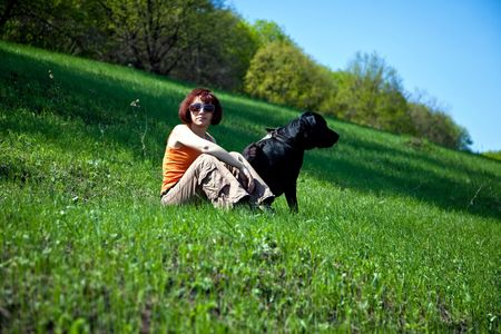 The young woman with black labrador on a green grass Stock Photo - 4831181