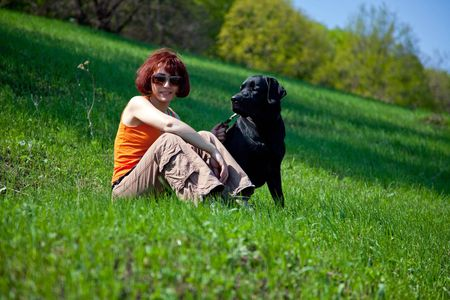 The young woman with black labrador on a green grass Stock Photo - 4831182