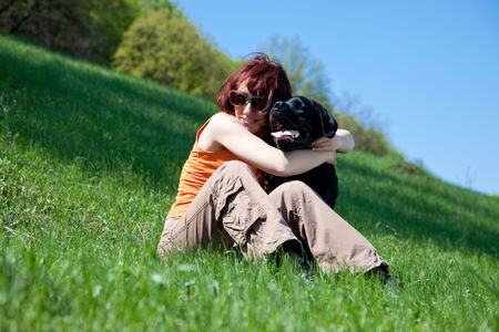 The young woman with black labrador on a green grass Stock Photo - 4831180