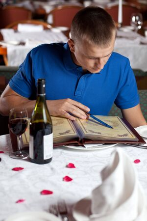 The man sits at a table in cafe and chooses meal under the menu Stock Photo