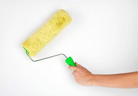 Hand with paintbrush roller on grey background Standard-Bild