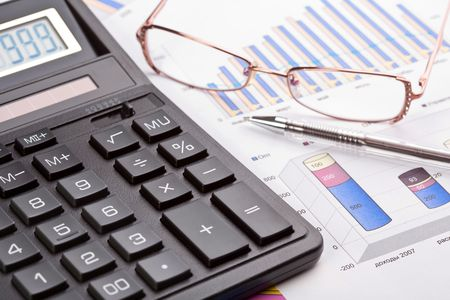 Financial work. The calculator, pen and female eyeglasses on business reports Stock Photo