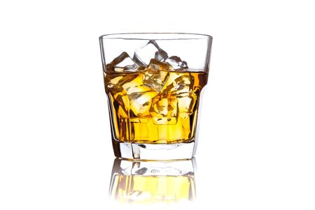 Glass of scotch whiskey and ice on white