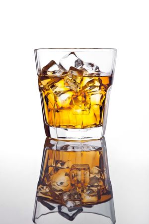 Glass of scotch whiskey and ice on glass table