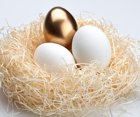 One golden egg and two white egg in the nest photo
