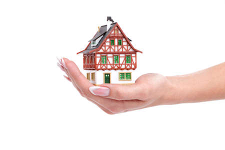 The house in woman hands on white Stock Photo - 8628870