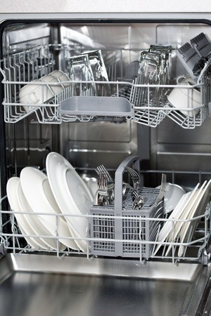 Dishwasher with white plates and steel cutlery photo
