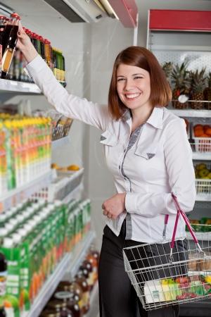Woman in a supermarket choosing bottle of juice
