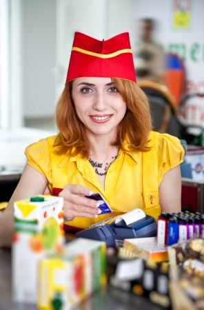 Smiling cashier girl in red and yellow uniform in supermarket photo