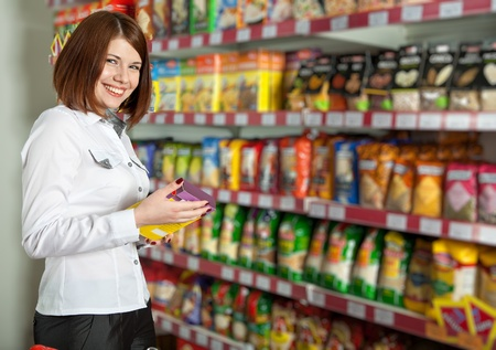 food additives: Pretty woman buyer in grocery shop at shelves with products