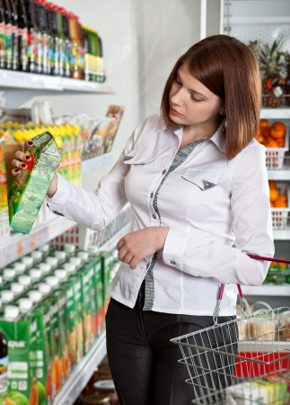 choose person: Woman in a supermarket choosing box of juice