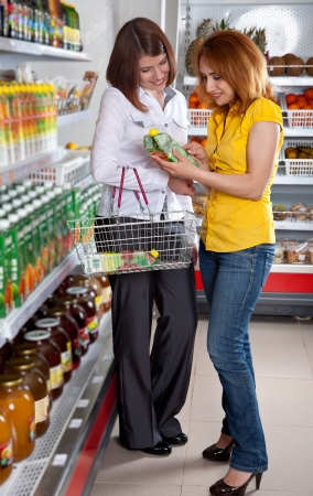 Two woman in supermarket choosing juice Stock Photo - 13698251