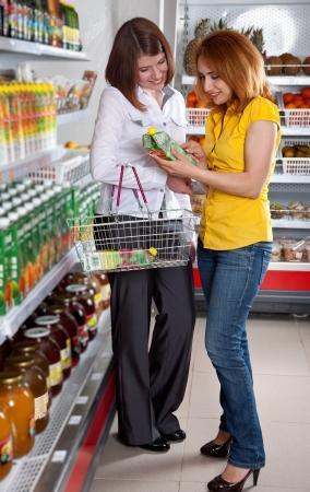 Two woman in supermarket choosing juice photo